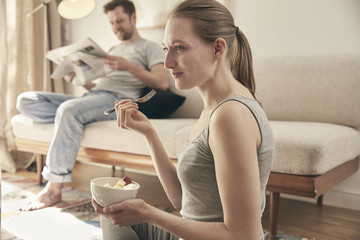 Woman eating fruits in living room with man in background