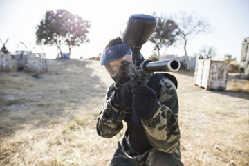 Paintball player aiming with paintball gun during a paintball game