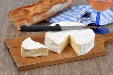 Camembert posé sur une planche à découper avec du pain et un verre de rosé