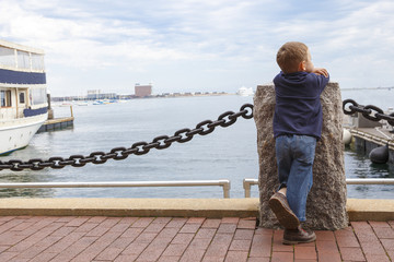 boy in harbor. little kid looking at ships and sea. empty space for your text