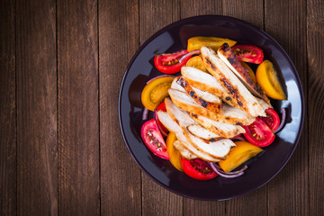 Sliced roasted chicken breast and fresh salad with tomato and purple onion top view on dark wood background. Healthy food. Space for text.