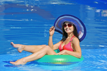 Young beautiful woman with inflatable circle in swimming pool