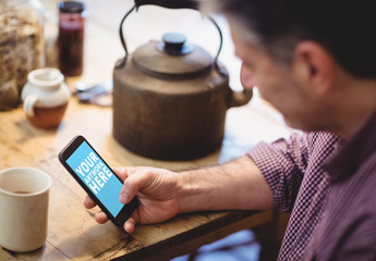 User with Smartphone at Wooden Table with Kettle Mockup