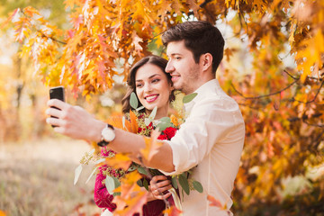 Stylish and romantic caucasian couple smiling and making selfie in beautiful autumn park. Love, relationships, romance, happiness concept. Bouquet in girl's hands.