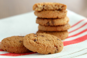 Chocolate chip cookies on white linen napkin on wooden tab