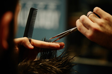Hands of a Barber the man in the process of cutting hair with scissors in Barbershop closeup