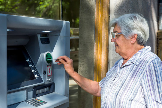 elderly woman inserting credit card to ATM