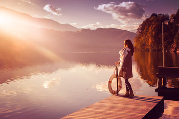 woman standing on a bridge by the lake in sunset