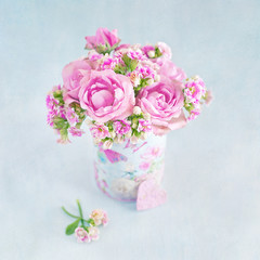 Lovely bunch of a pink flowers in a vase ,decorated with a heart on a table .