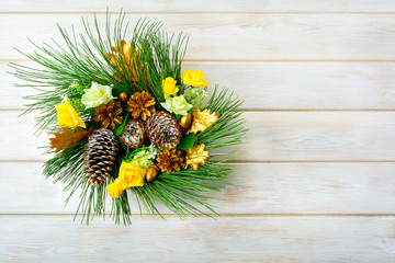Christmas wreath with yellow silk roses and golden pinecones