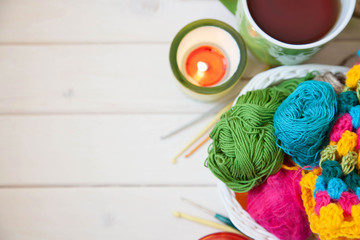 Colored candle holders and yarn for knitting.The white basket crochet fabric and colored yarn.
