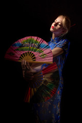 girl in japanese costume dancing with fans on black background