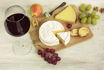 Red wine with many different types of cheeses and grapes
