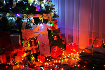 Boxes with presents under Christmas tree, close up view