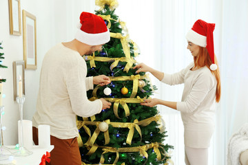 Young man and woman decorating Christmas tree in living room