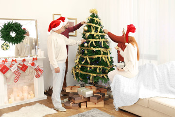 Happy family decorating Christmas tree in living room