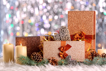 Christmas composition with gift boxes, candles and decorations on bokeh background