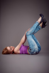 Slim beauty woman lying on a floor in sexy jeans on grey background