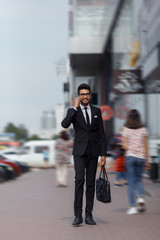 Businessman walking down the street and talking on the phone. Blurred motion.