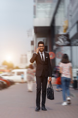 Businessman walking down the street and talking on the phone  with early sunlight. Blurred motion.