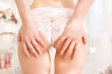 Woman pawing her perfect buttocks. Nude female ass in white lace panties with hands on it close-up. Sex, temptation, passion, seduction concept