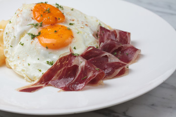 Appetizing Spanish Iberian cured ham with fried egg and chips on
