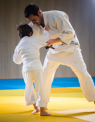Man and young boy are training judo throw