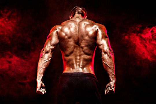 The back view of torso of attractive male body builder on dark smoky background.
