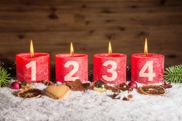 Angezündete vierte Adventskerze in Schnee