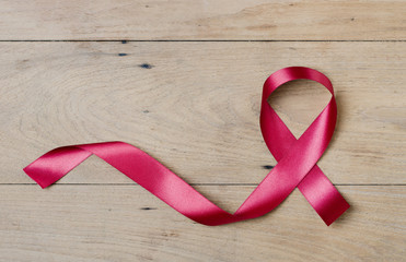 Red ribbon on wood table at top view