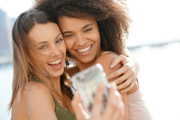 Attractive girls taking selfie picture with smartphone