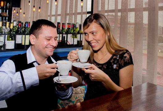 Девушка и молодой человек в кафе,  улыбаются  и пьют кофе