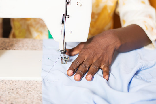 closeup of the woman's hand behind a sewing machine.
