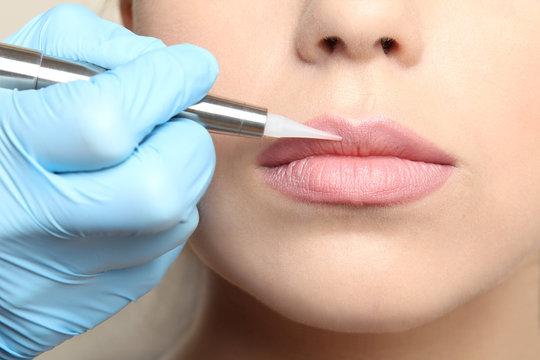 Cosmetologist making permanent  make up on lips, close up