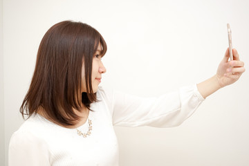 Young woman taking a selfie with her smart phone