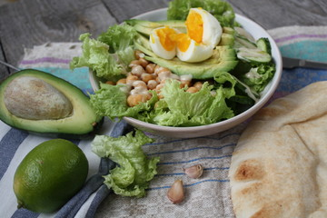 healthy salad in a bowl. avocado, chickpeas, cucumber and egg. more greens every day