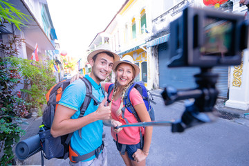 Tourism and technology. Traveling backpacker couple taking selfie on action camera together outdoors.