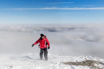 Male hiker in Carpathian mountains on top of snowy peak