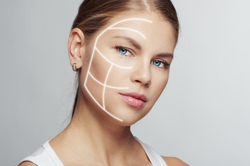 Close-up of attractive young female with light lines on her face. Concept of skin treatment, face rejuvenation and plastic surgery.
