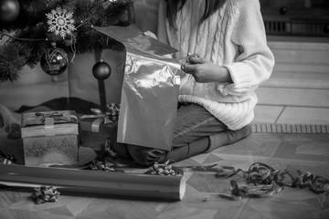 Closeup monochrome image of girl preparing Christmas gifts