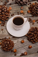 Small white cup of coffee, cocoa beans, hazelnuts, cone on wooden background