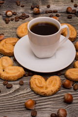 Small white cup of coffee, hazelnuts, cocoa beans, cookies on wooden background