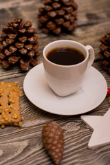 Small white cup of coffee, cocoa beans, hazelnuts, cookies, cone, christmas decoration on wooden background