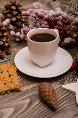 Small white cup of coffee, cocoa beans, hazelnuts, cookies, cone, christmas decoration, fir branch in snow on wooden background