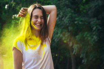 Emotional young woman with colorful powder Holi