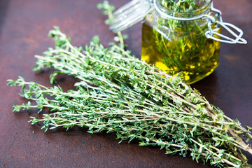 Thyme oil. Thyme essential oil jar glass bottle and branches of