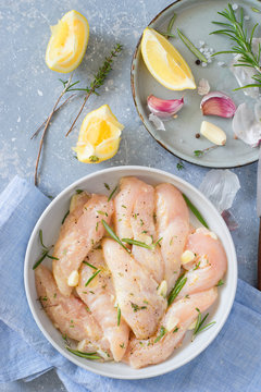 Raw chicken tenders marinated with garlic, olive oil, lemon juice, rosemary, thyme, salt and pepper