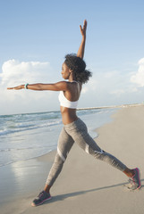 Stretching young woman wearing fitness gadget