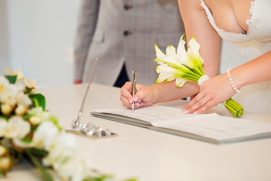 Bride hand with a pen signing wedding license. Marriage contract