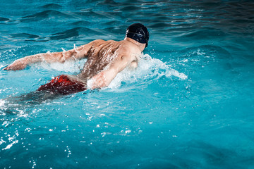 Young healthy man with muscular body swims